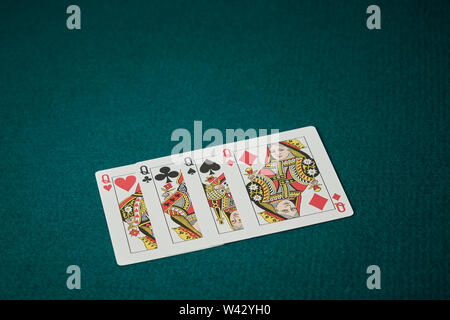 poker game of queens displayed the cards on green carpet in the background - Stock Image