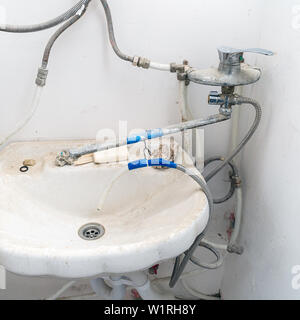 Old dirty sink with wrong connection of pipes and other plumbing - Stock Image