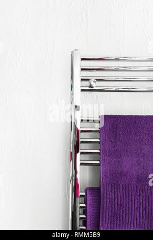 Purple fluffy terry towels hanging on stainless steel warmer rack installed in bathroom. White wall background. Interior design wellness hotel home de - Stock Image