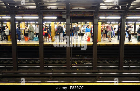 People waiting for a train on a subway platform in New York City - Stock Image