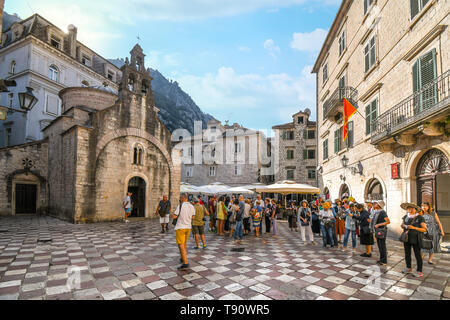 Tourists gather on St Luke's square in front of the old church with it's three bell towers in Kotor, Montenegro. - Stock Image