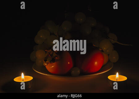 Playing with candles light a new world appears from the shadow... Easy stuffs as fruits can become new objects speaking of mind. - Stock Image