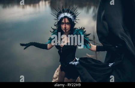 A young woman in the image of a fairy and a sorceress standing over a lake with the reflection of the clouds in a black dress and a crown. - Stock Image
