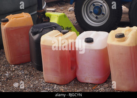 A line of plastic gallon containers holding industrial fluids in front of a vehicles wheels and lifting arms on a gravel track. - Stock Image
