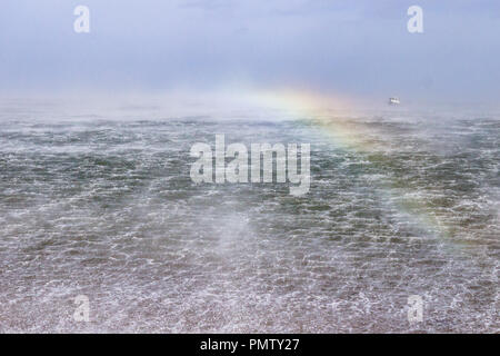 Rainbow effect over the sea as waves and spray whipped up by strong winds during Storm Ali catch the sunlight. Low Newton by the Sea, Northumberland, UK. 19th September 2018. - Stock Image