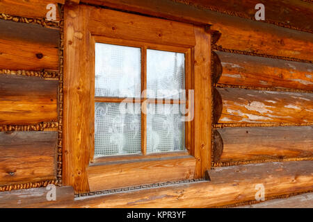 In the wall made of wooden logs, there is a small window in the wooden frame. This is an example of a typical architectural - Stock Image