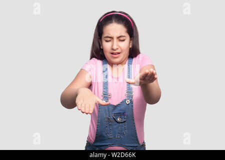 Portrait of closed eyes blind brunette young girl in casual pink t-shirt and blue denim overalls standing and try to touch or find something . indoor - Stock Image
