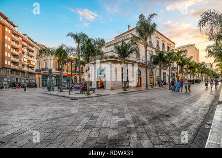 Shops line the main street, Corso Umberto, as locals enjoy an early evening stroll, or Passeggiata, in Brindisi Italy, in the Puglia Region. - Stock Image
