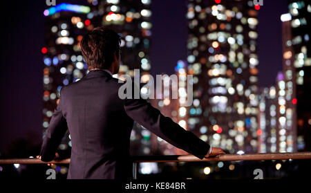 Back of businessman watching night view of city - Stock Image