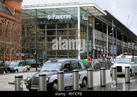 View of street with taxis waiting parked outside St Pancras Station building on Pancras Road at Kings Cross & tourist Big Bus London UK  KATHY DEWITT - Stock Image