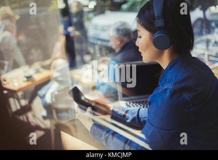 Young woman listening to music with headphones, texting with cell phone at cafe window - Stock Image