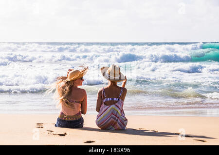Friends outdoor people with girls young couple sitting on the sand at the beach enjoying the sea and the summer vacation - viewed from back - outdoor  - Stock Image