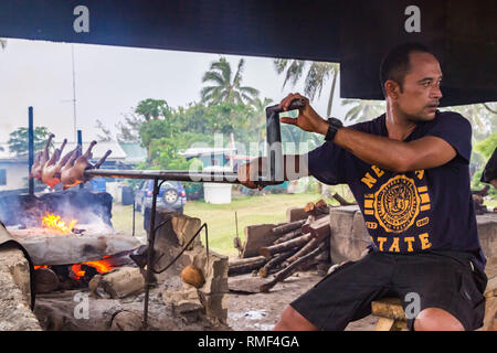 Tongatapu, Tonga - Jan 3 2014: a local native indigenous Polynesian man roasts a pork barbecue of a piglets on an open fire made of coconut shells on  - Stock Image