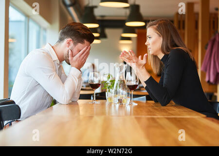 Young couple arguing about jealousy in the restaurant over a glass of wine - Stock Image