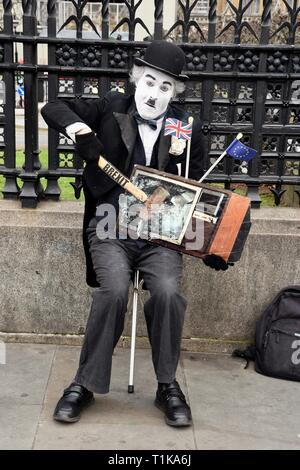 Westminster, London, UK. 27th Mar 2019. Remain Protester. A Charlie Chaplin actor 'smashes' a TV Screen with a hammer marked Brexit. Houses of Parliament, Westminster, London. UK Credit: michael melia/Alamy Live News - Stock Image