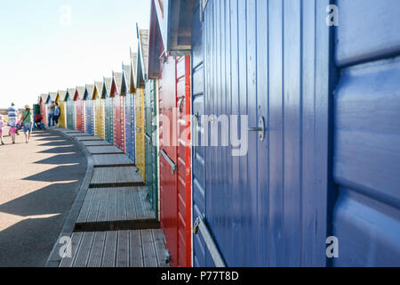 Family walking by colourfully painted beach huts in Dawlish Warren on a bright and sunny day close to the beach, Devon, England, Europe. - Stock Image
