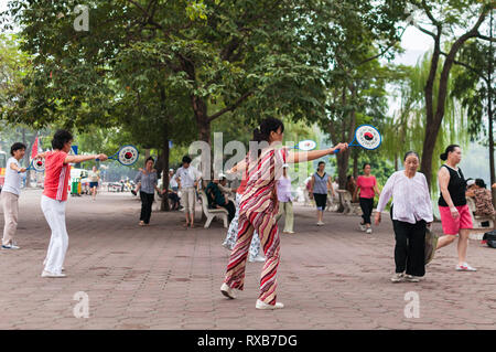 A group of women exercising to music at Hoan Kiem Lake in the morning, Hanoi, Vietnam - Stock Image
