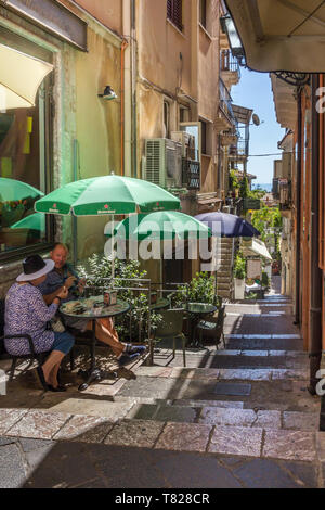 Taormina, Sicily - 22nd September 2017: Small cafe restaurant in a narrow alley off the Corso Umberto This is the main street through the town. - Stock Image
