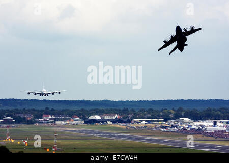 Airbus A380-841 landing and Airbus A400M Atlas taking off at runway of Farnborough International Airshow 2014 - Stock Image