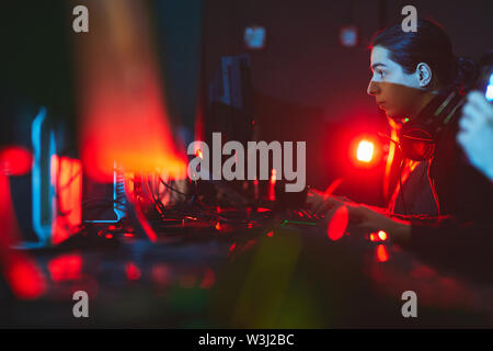 Serious geek boy with ponytail sitting at table in red light and typing on keyboard while playing network game in computer club - Stock Image