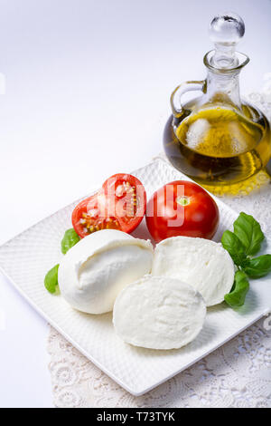 Soft white Italian cheese Mozzarella buffalo served with fresh tomato, olive oil and green basil leaves on white background - Stock Image