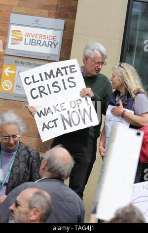 An Activist from the Climate Change group Extinction Rebellion holds a banner saying ÒClimate Crisis wake up no act nowÓ during a demo outside Derby City Council house on 22/05/2019 - Stock Image