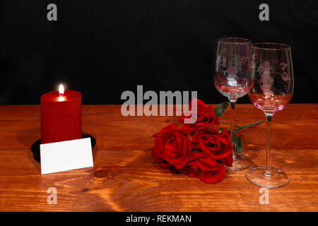 Beautiful etched wine glasses with red roses and red candle on wooden table and dark background. Valentines, Mothers Day, Easter, Christmas, Wedding C - Stock Image