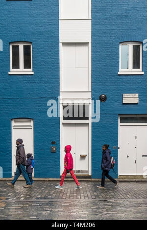 A family walking past a house painted in blue and white in Clink Street in London. - Stock Image