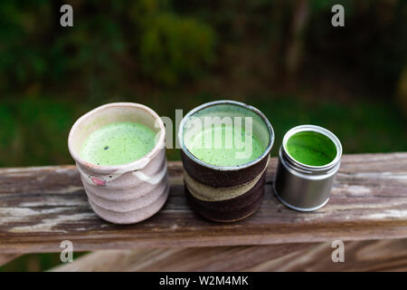 Wooden railing on backyard deck garden and two cups with Japanese vibrant green tea matcha foam in morning and tin container - Stock Image