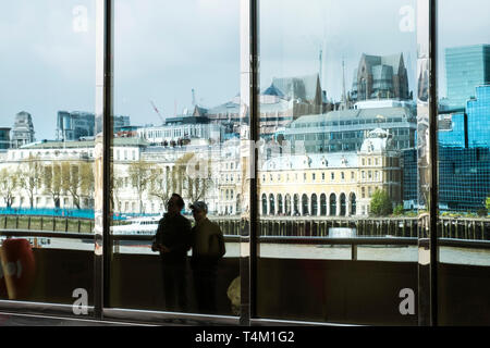 The distorted reflections of buildings on the Embankment seen in large glass windows in a building on the South Bank in London. - Stock Image