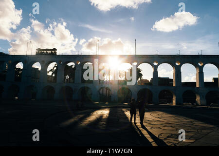 19th-century colonial Lapa Arches, Rio de Janeiro, Brazil - backlit with sun rays coming through one of the openings - Stock Image
