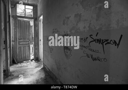 Interior of ruined facilities covered by graffiti at the Canfranc International railway station (Canfranc, Pyrenees, Huesca, Aragon,Spain) B&W version - Stock Image