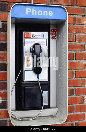 An old fashioned pay phone on a brick wall outside a convenience store in Indian Lake, NY USA - Stock Image
