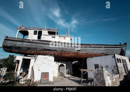 Wooden fishing boat on roof of house two kilometres from the coast, after a December 26, 2004 tsunami in Banda Aceh, Indonesia - Stock Image