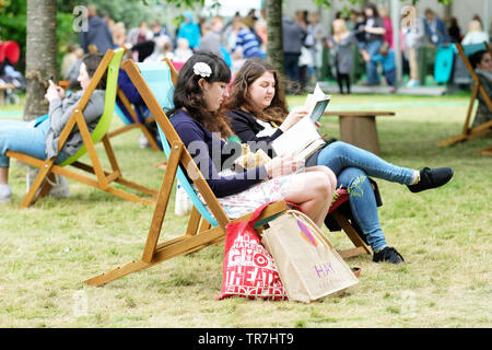 Hay Festival, Hay on Wye, Powys, Wales, UK - Thursday 30th May 2019 - Visitors enjoy a chance to sit and read on the Festival lawns between sessions and events at the 32nd Hay Festival on a cool breezy day. Photo Steven May / Alamy Live News - Stock Image