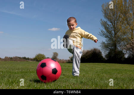 toddler kicking ball in field - Stock Image