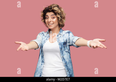 Portrait of happy young woman with curly hair in casual shirt standing with wide raised arms and looking at camera with toothy smile sharing something - Stock Image