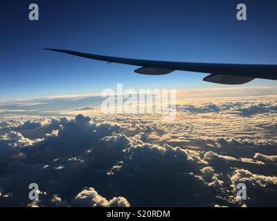 Plane wing flying through clouds - Stock Image