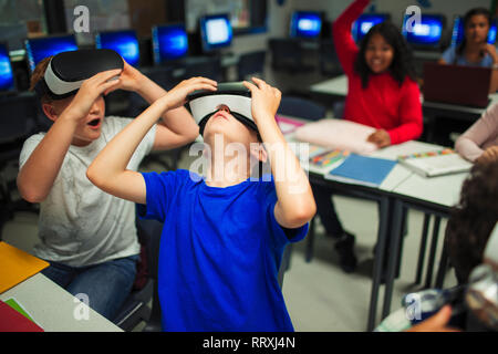 Curious junior high school boys using virtual reality simulators in classroom - Stock Image