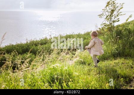 Baby boy (18-23 months) walking towards sea - Stock Image