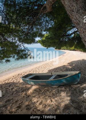 Small boat on beach under pine trees in Tucepi, Croatia - Stock Image