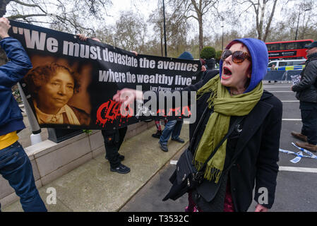 London, UK. 6th April 2019.  Class War call on the other protesters to follw them after they thave pushed aside the barriers keeping the protest away from the Dorchester Hotel. The protest was against the hotel ownner, the multi-billionaire Sultan of Brunei who has announced death by stoning as a punishment for gay sex, adultery and blasphemy demonstrating against this barbaric abuse of international law and human rights. Protesters called for a boycott of his hotels around the world. Peter Marshall/Alamy Live News - Stock Image