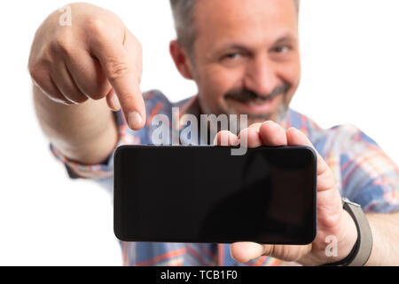 Closeup of smiling man pointing index finger at telephone display isolated on white studio background - Stock Image
