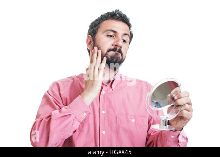 Young handsome man checking his face skin and touching his beard - Stock Image