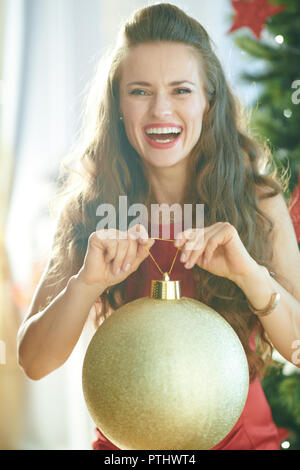 happy trendy woman in red dress near Christmas tree holding big gold Christmas ball - Stock Image