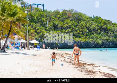 Mother and son play football soccer on West Bay Beach Roatan Honduras. - Stock Image