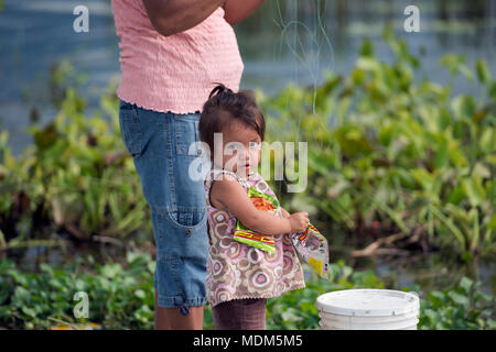 A young, indigenous Itza Maya girl eats candy while her mother fishes in Lake Peten, northern Guatemala. - Stock Image