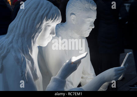 Amsterdam Light festival with detail of artwork Absorbed by Light of Gali May Lucas (UK), smartphone users with faces lit up by screens. - Stock Image