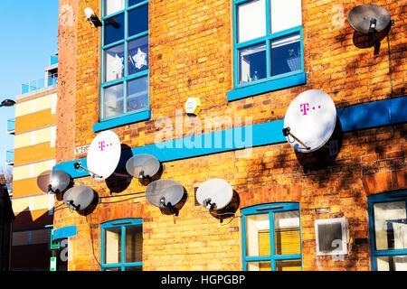 Satellite dishes TV receivers satellite dish on wall TV reception BskyB satellites UK England - Stock Image