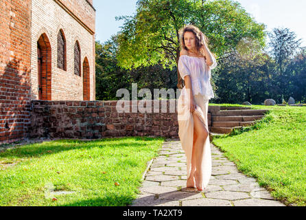 young girl in a light dress standing on the alley in the park on sunny summer day - Stock Image